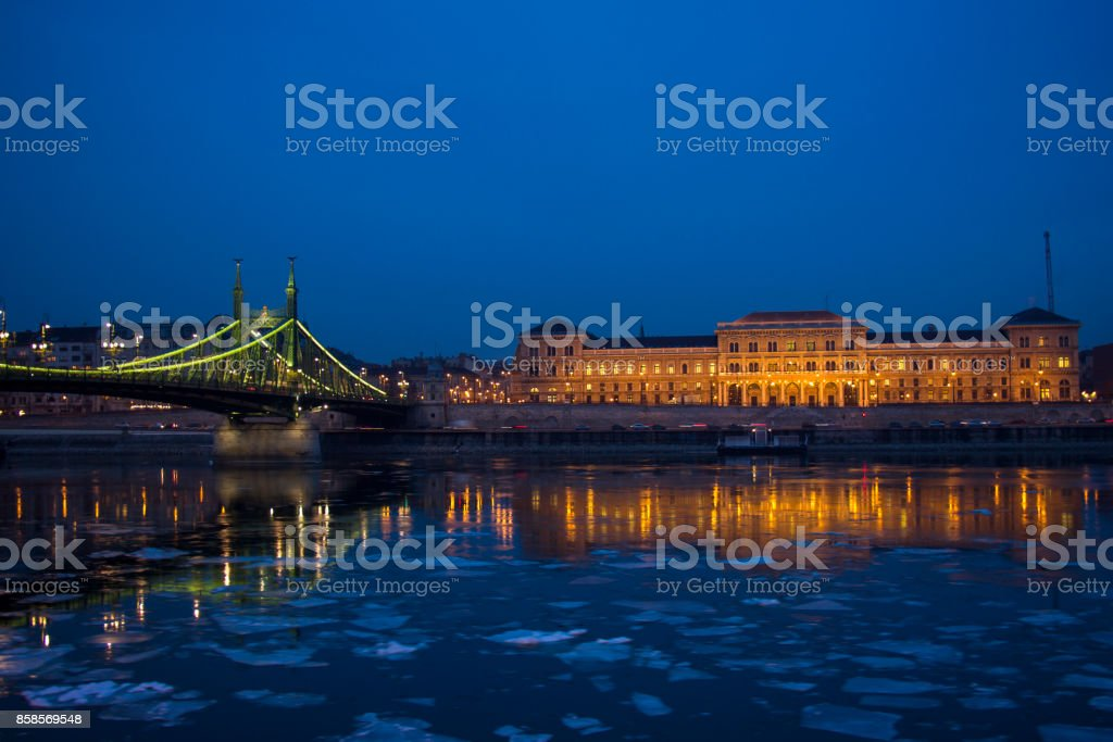 Liberty Bridge and Budapest Corvinus University at nightime stock photo