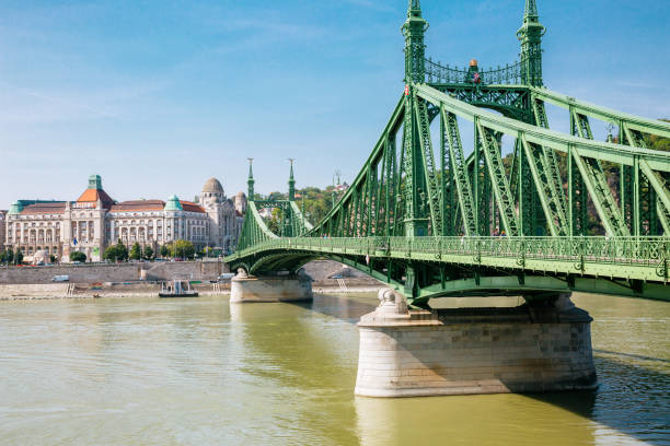 Liberty bridge in Budapest Liberty bridge - view from the Pest side. Gallery hotel on the background. Liberty Bridge is the third and shortest bridge of Budapest. It was built for the Millennium World Exhibition in 1896, its original name being Francis Joseph Bridge. liberty bridge budapest stock pictures, royalty-free photos & images