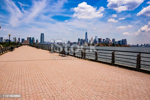 A view of the promenade of Liberty State Park in New Jersey with the view of  the Lower Manhattan skyline to the right and the Jersey City skyline towards the end of the walkway. Located in southern Jersey City, Liberty State Park is an important attraction because of its panoramic view of Manhattan, specially Lower Manhattan and Jersey City and because it is very close to Liberty Island where the Statue of Liberty is located. Ferry boats shuttle to Liberty Island from nearby Liberty State Park