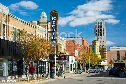 Ann Arbor, United States - October 18, 2015: People walking in the sidewalk of Liberty Street in Downtown Ann Arbor, with storefronts and the Michigan Theater sign, State Theater sign, cars and parked bicycles in the scene, and the Burton Memorial Tower in the distance, during a day with a blue sky with clouds.