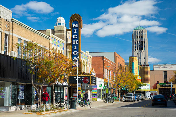 Liberty Street Scene in Ann Arbor Ann Arbor, United States - October 18, 2015: People walking in the sidewalk of Liberty Street in Downtown Ann Arbor, with storefronts and the Michigan Theater sign, State Theater sign, cars and parked bicycles in the scene, and the Burton Memorial Tower in the distance, during a day with a blue sky with clouds. ann arbor stock pictures, royalty-free photos & images