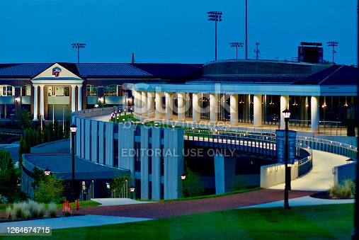 Lynchburg, Virginia / USA - June 29, 2020: Lights illuminate the Liberty Baseball Stadium (l) and the Liberty Athletic Center (r) as night falls across the Liberty University campus.