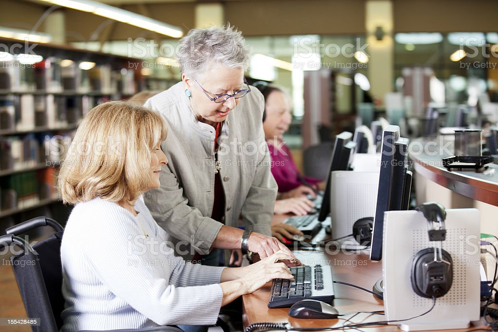 Librarian helping a group of seniors working on computers stock photo