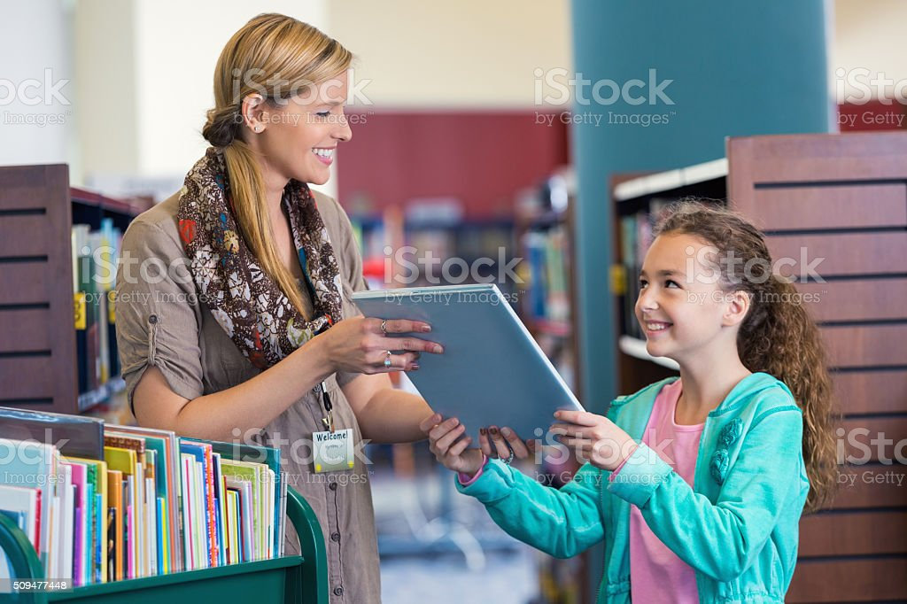 Librarian helping elementary age little girl with book selection stock photo