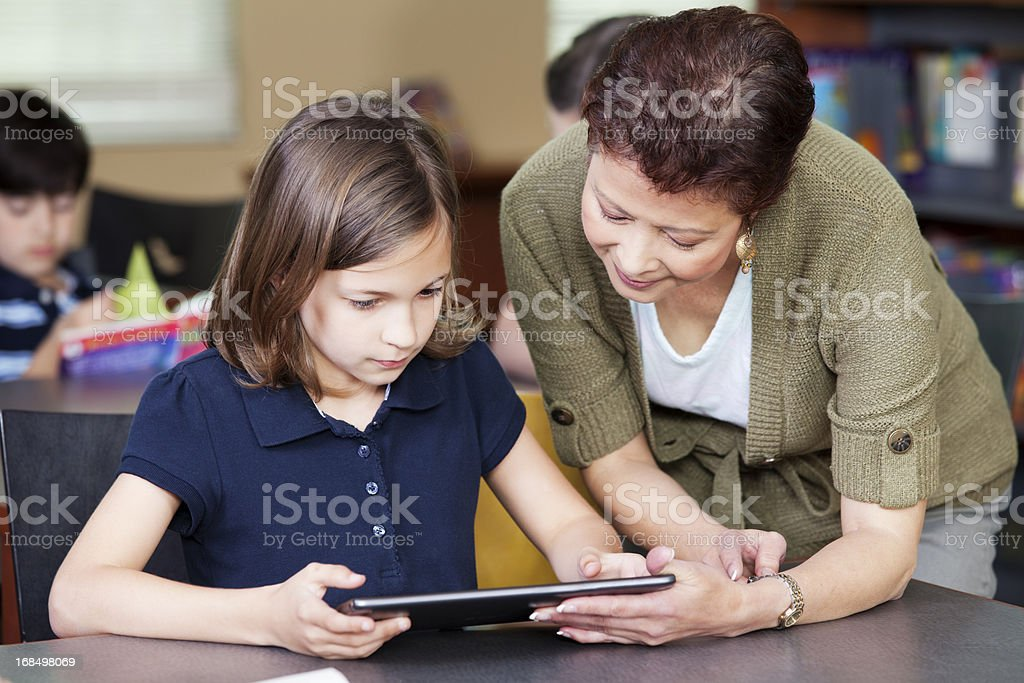 Librarian helping elementary student with project on digital tablet royalty-free stock photo