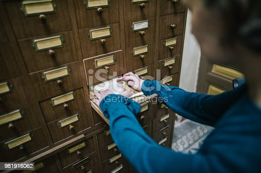 668340340istockphoto Librarian looking for the index card in the old register 981916062