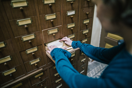668340340 istock photo Librarian looking for the index card in the old register 981916062