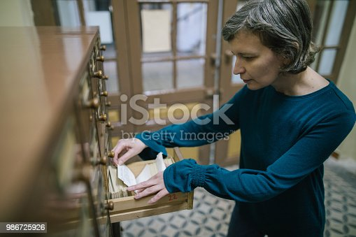 668340340istockphoto Librarian looking for the index card in the old register 986725926