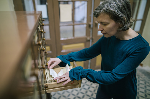 668340340 istock photo Librarian looking for the index card in the old register 986725926