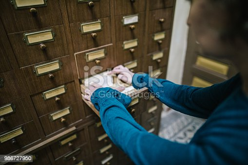 668340340istockphoto Librarian looking for the index card in the old register 986727950
