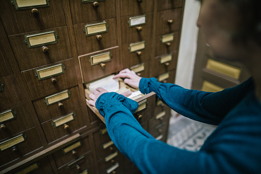 668340340 istock photo Librarian looking for the index card in the old register 986727950