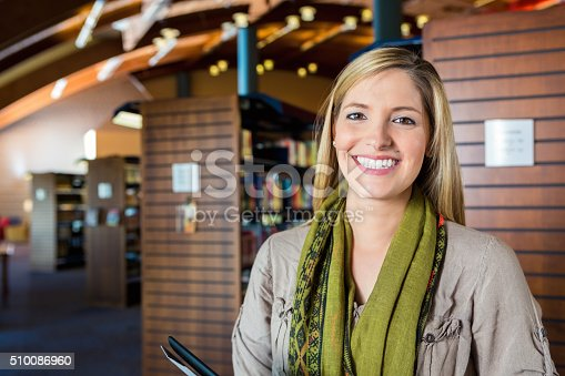 Mid adult Caucasian woman is looking at the camera and smiling. Librarian or library patron is holding a digital tablet. She is standing in front of rows of tall bookshelves. Wide angle view shows beautiful architecture in modern library.
