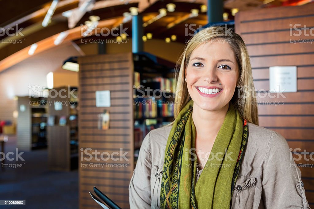 Librarian or patron standing in large modern public library stock photo