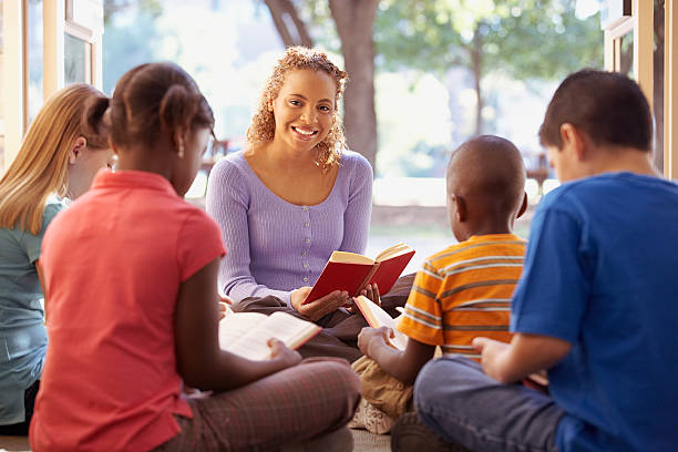 Librarian reads aloud to a group of children stock photo