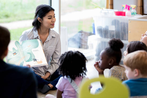 Librarian reads children a book during story time Confident female librarian reads young schoolchildren a picture book during story time. preschool teacher stock pictures, royalty-free photos & images