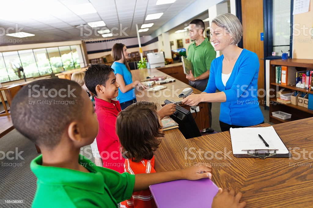 Librarian teacher helping students check out books in school library stock photo