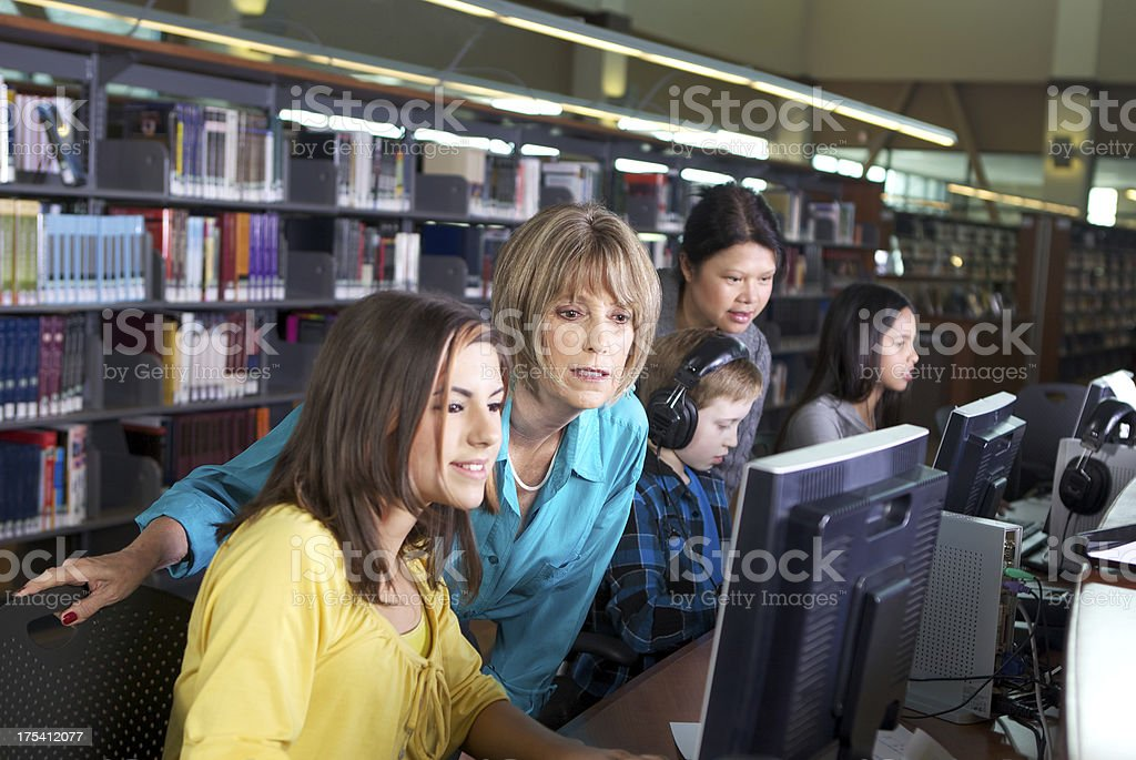 Librarian Working with Student on Computer at a Library stock photo