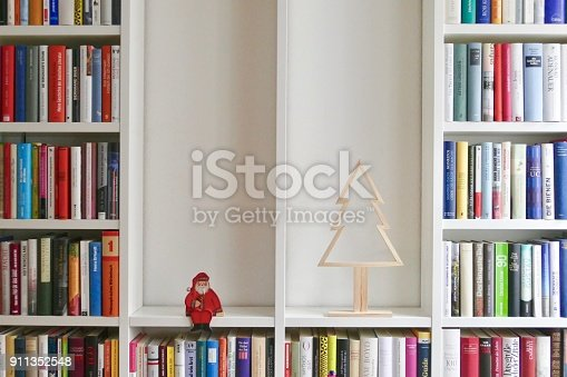 1057183432 istock photo Library book shelves packed with colorful books and empty parts showing santa claus and abstract christmas tree 911352548