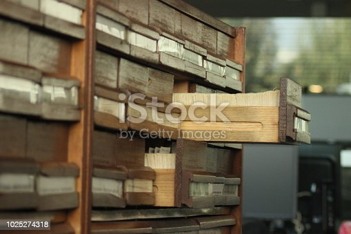 Close up of old wooden vintage Library Catalog card shelves, nearby a modern computer set