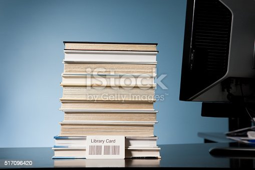 A stack of books on a library checkout counter. (code on library card created by photographer)