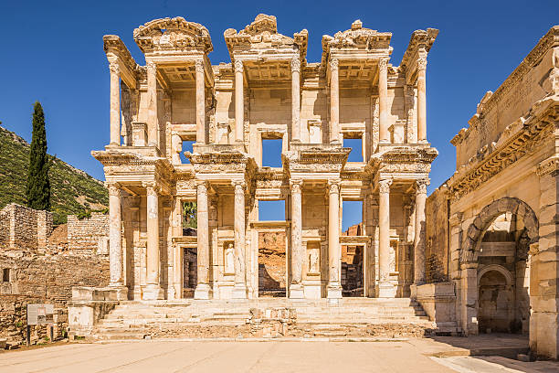 Library Of Celsus at Ephesus The front facade and courtyard of the library building at Ephesus is an imposing ancient Greek and Roman structure. Built from old stone and reconstructed by archaeologists, it is a popular tourist stop near the city of Izmir in Turkey. celsus library stock pictures, royalty-free photos & images