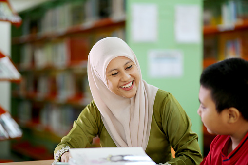 A Muslim female adult is guiding a young boy for his homework in library.