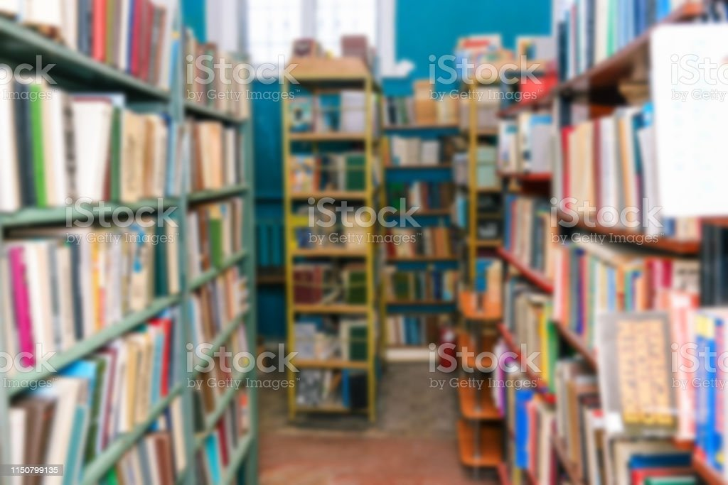 Library room Pass along the bookshelves. Selling books or getting...