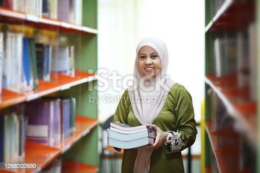 A Muslim female adult is choosing book from library book shelf in Malaysia.