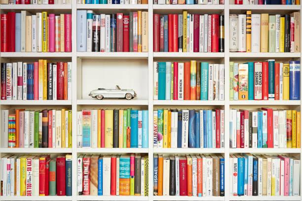 Bibliothek, weiße Regale, mehrfarbige Bücher, ein Teil gefüllt mit generischen Cabrio-Auto – Foto