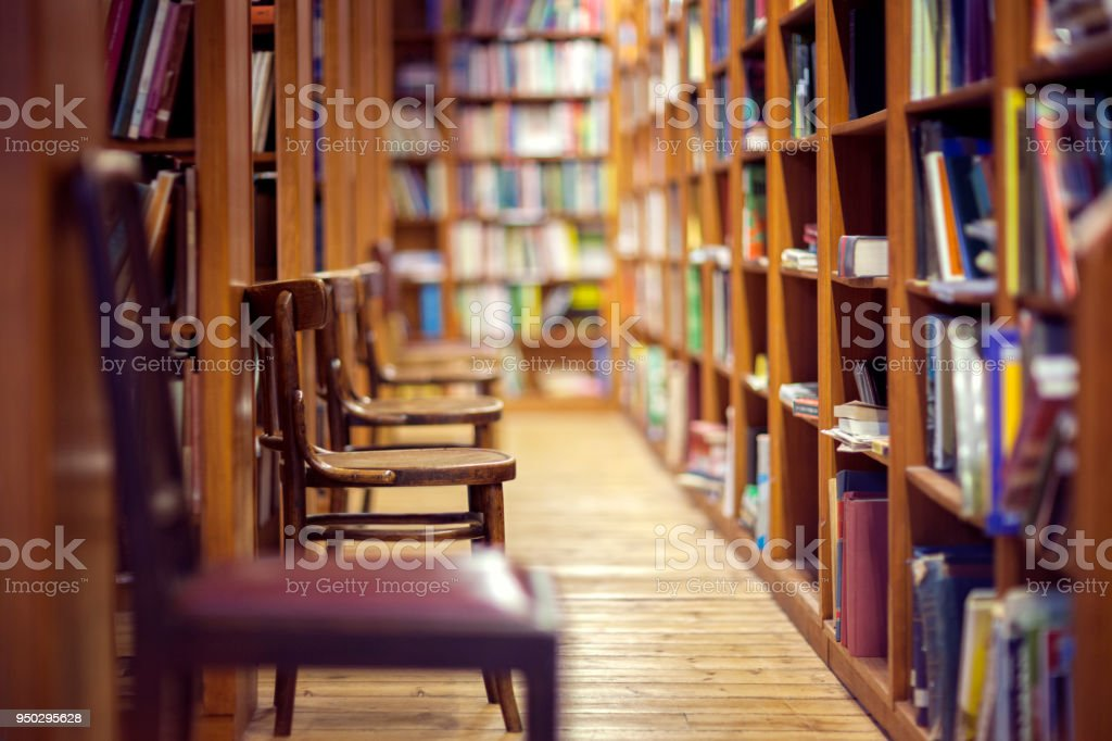 Library with books on shelf and empty chairs stock photo