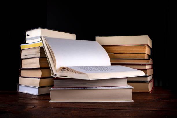 Libro aperto su una catasta di libri Libro aperto su una catasta di libri con sfondo nero libro stock pictures, royalty-free photos & images
