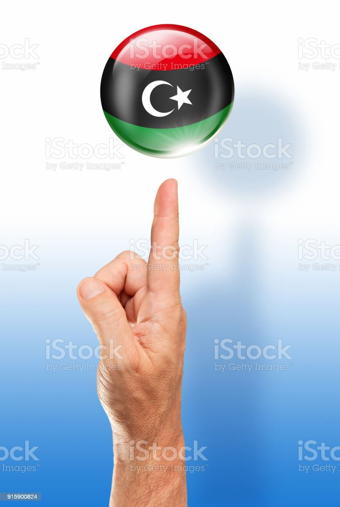 Libya button libyan flag pointing with human hand stock photo