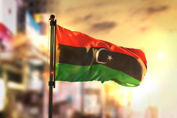 Libya Flag Against City Blurred Background At Sunrise Backlight stock photo