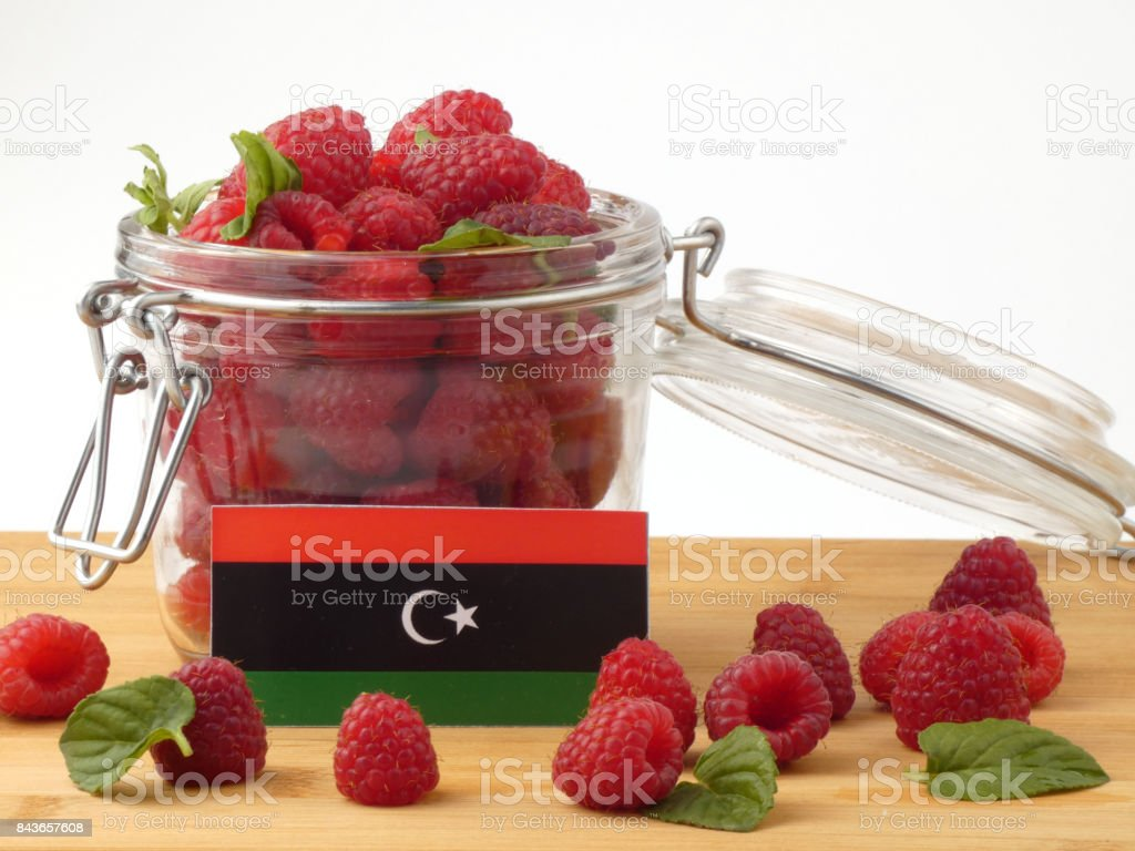 Libyan flag on a wooden panel with raspberries isolated on a white background stock photo