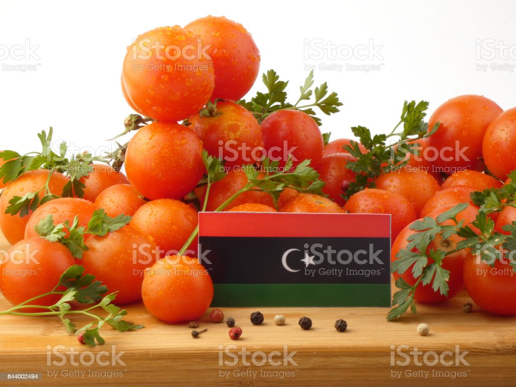 Libyan flag on a wooden panel with tomatoes isolated on a white background stock photo