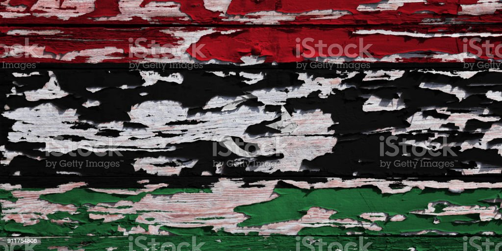 Libyan flag painted on a grunge plank stock photo