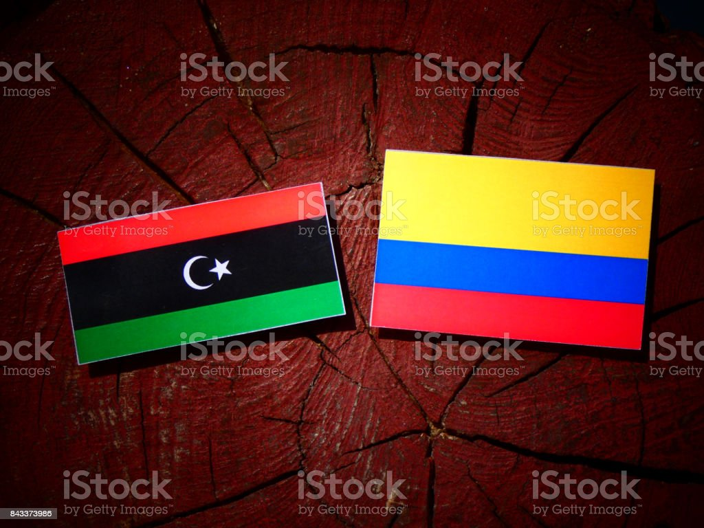 Libyan flag with Colombian flag on a tree stump isolated stock photo