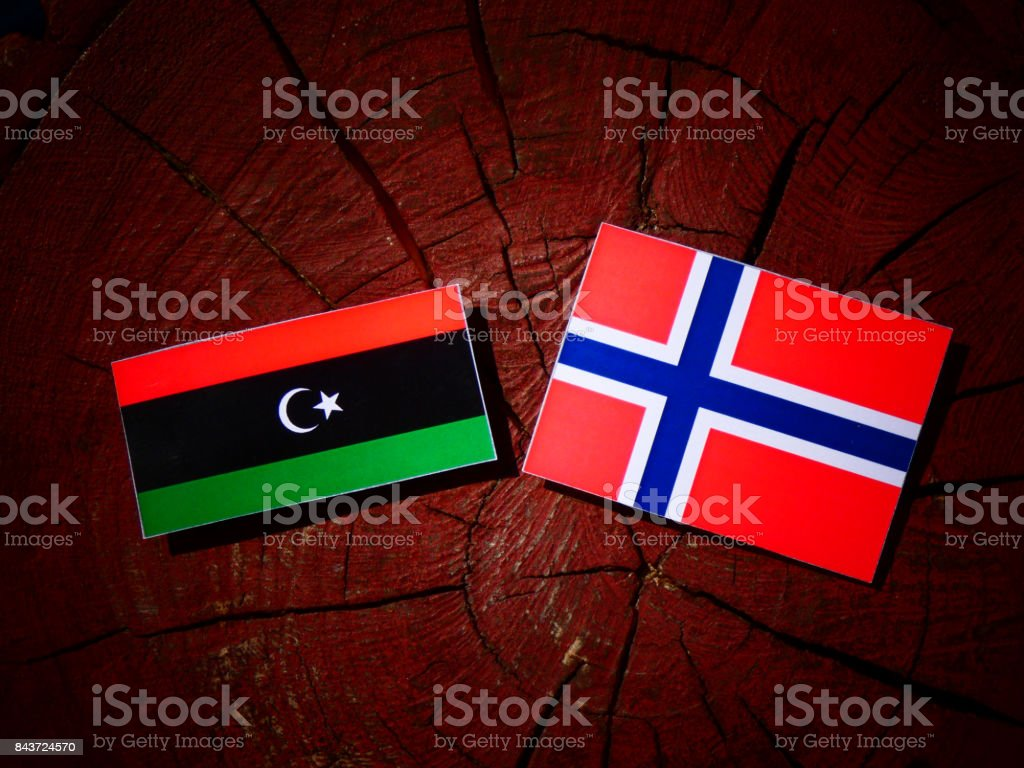 Libyan flag with Norwegian flag on a tree stump isolated stock photo