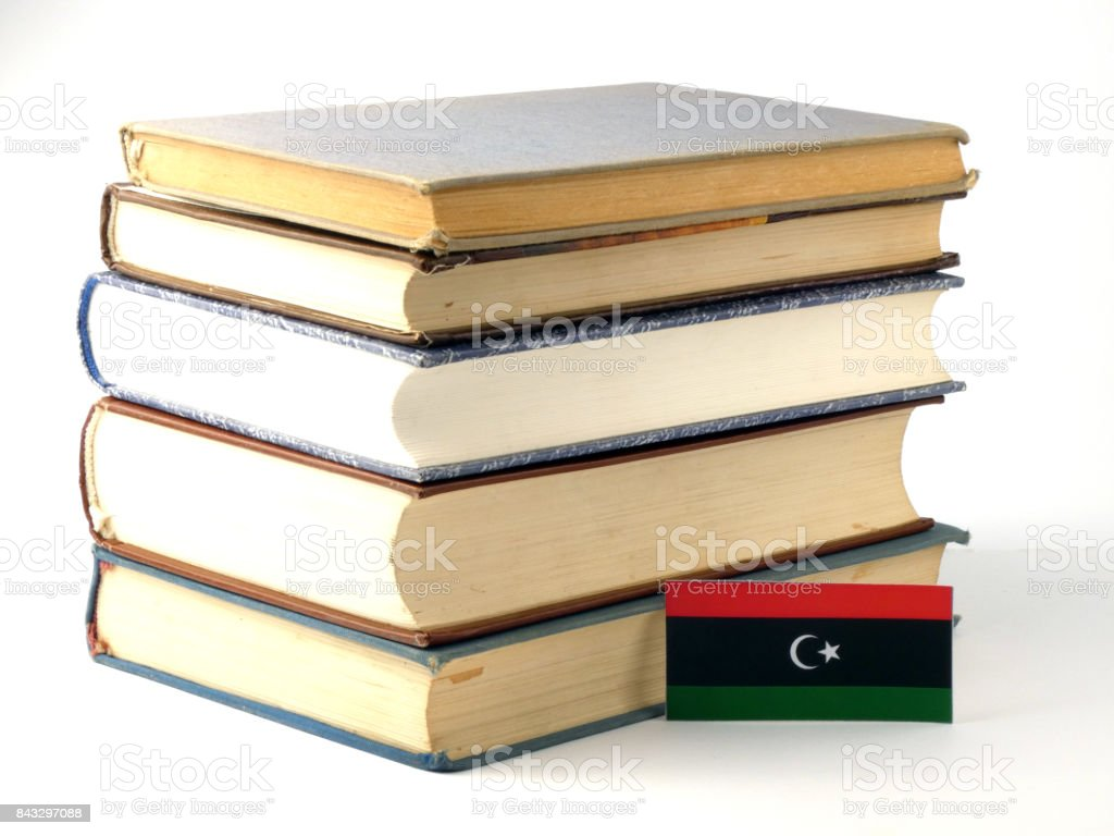 Libyan flag with pile of books isolated on white background stock photo