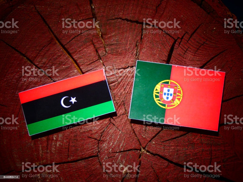 Libyan flag with Portuguese flag on a tree stump isolated stock photo