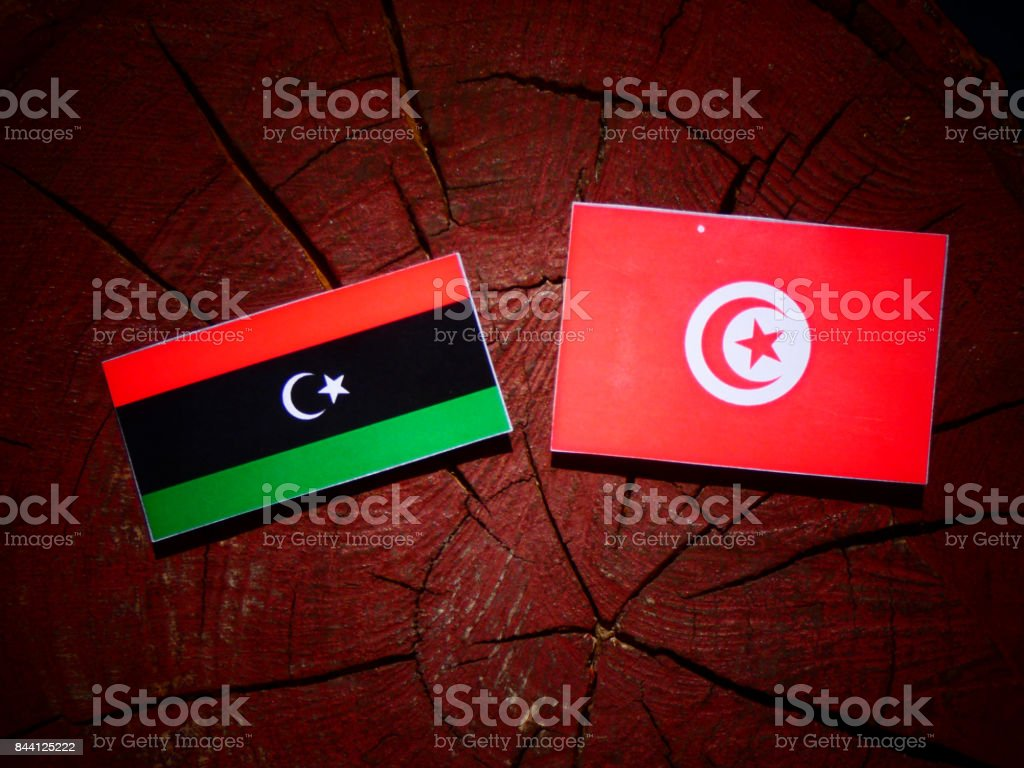 Libyan flag with Tunisian flag on a tree stump isolated stock photo