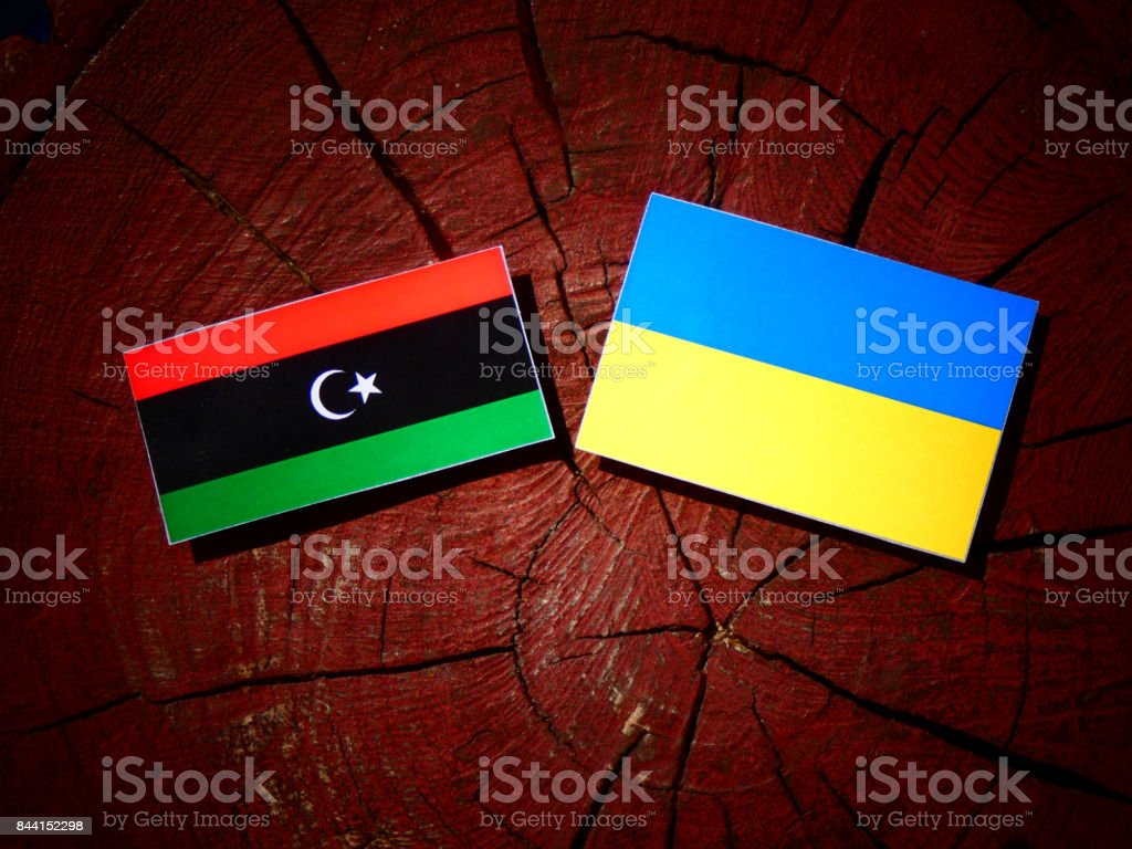 Libyan flag with Ukrainian flag on a tree stump isolated stock photo