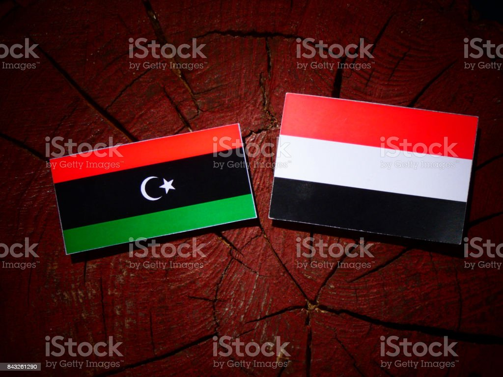 Libyan flag with Yemeni flag on a tree stump isolated stock photo