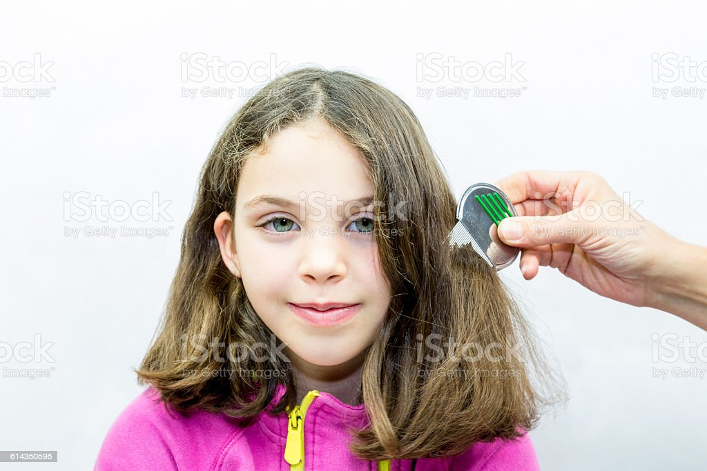Lice treatment. Girl gets combed for lice. royalty-free stock photo