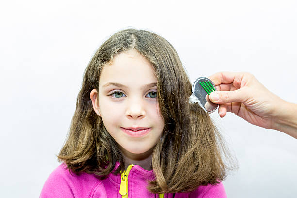Lice treatment. Girl gets combed for lice. stock photo