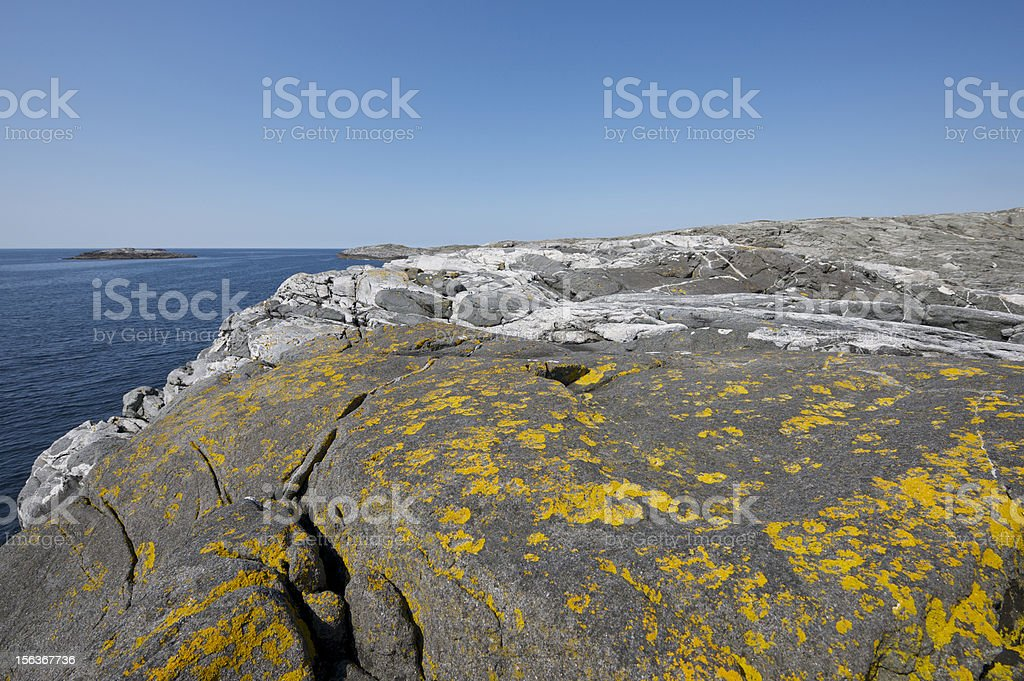 Lichen-covered cliffs of Norwegian coastline on a beautiful day royalty-free stock photo