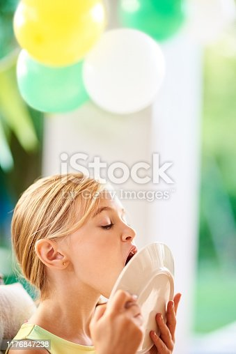 Shot a young girl licking a plate and enjoying the last bit of her cake