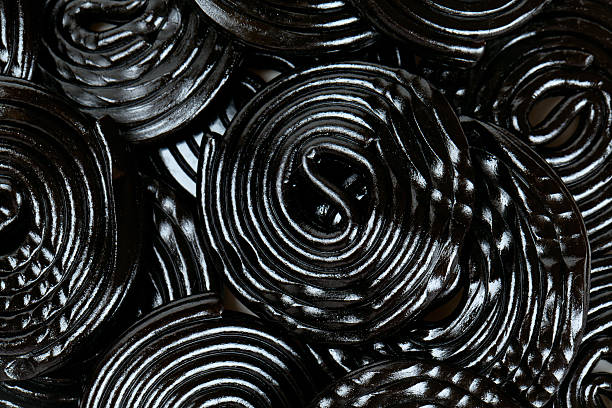 caramelle di liquirizia sola su sfondo bianco - liquirizia foto e immagini stock