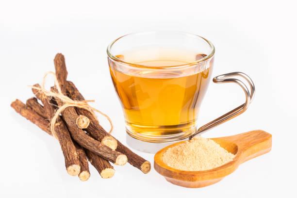 licorice cup of tea, powder and roots - glycyrrhiza glabra - liquirizia foto e immagini stock