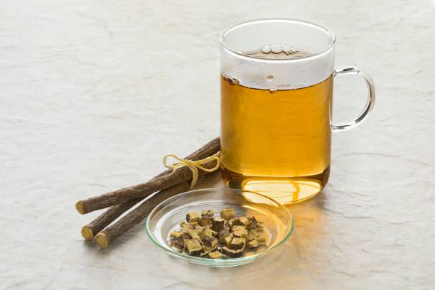 licorice tea and a heap of roots - liquirizia foto e immagini stock